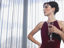 Woman With Champagne In Front Of Curtains Royalty Free Stock Image