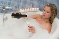 Woman with champaigne in bathtub. Young attractive woman with bottle of champaigne in bathtub Stock Photos