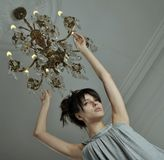 Woman with chandelier. Young woman with luxury chandelier Stock Photography