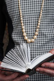 A woman in a Chanel-style reading a book Royalty Free Stock Photography