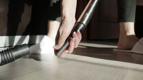 A woman changes the nozzle on the vacuum cleaner while cleaning the house. Women use vacuum cleaner to cleaning the floor in living room at home during end of stock footage