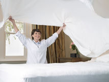 Woman With Changing Bed Sheet Stock Photography