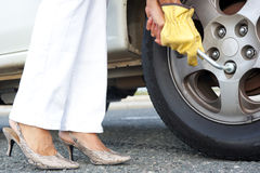 Woman changing car tyre Stock Photography
