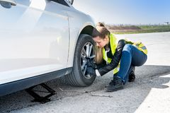 Woman changing damaged wheel and fixing it royalty free stock images