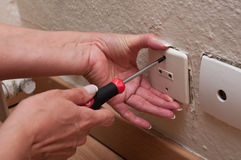 Woman changing a electrical outlet. Closeup woman changing a electrical outlet royalty free stock image