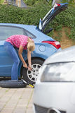 Woman Changing Flat Tyre On Car Stock Photo
