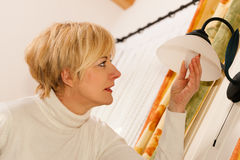 Woman changing a light bulb Stock Photo