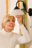 Woman changing a light bulb Royalty Free Stock Photos