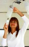 A woman changing light bulb. A beautiful woman changing light bulb Stock Photo