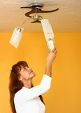 A woman changing light bulb Stock Photo