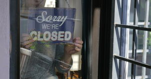 Woman changing sign from closed to open stock video footage