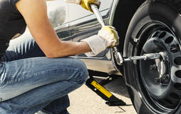 Woman changing tire car. Woman is changing  tire of her car with wheel wrench Royalty Free Stock Image
