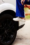 Woman is changing tire of car with wheel wrench Royalty Free Stock Photo