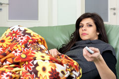 Woman changing tv channels. Bored young woman holding remote-control and watching tv at home Royalty Free Stock Photo