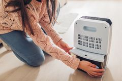 Woman changing water container of dehumidifier at home. Dampness in apartment. Modern air dryer. Technology royalty free stock photo