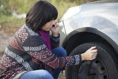 Woman changing a wheel on a car on the empty road. Selective focus and small depth of field Royalty Free Stock Images