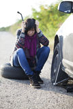 Woman changing a wheel on a car on the empty road. Selective focus and small depth of field Stock Photography