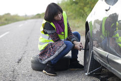 Woman changing a wheel on a car on the empty road. Selective focus and small depth of field Royalty Free Stock Image