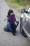 Woman changing a wheel on a car on the empty road. Selective focus and small depth of field Royalty Free Stock Photo