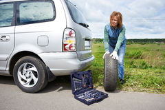 Woman changing a wheel of car. On road Royalty Free Stock Images