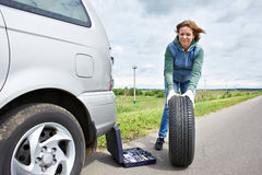Woman changing wheel of car. Woman changing a wheel of car on road Royalty Free Stock Photography