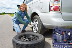 Woman changing a wheel of car. On road Royalty Free Stock Photos