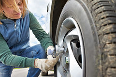 Woman changing wheel of car. Woman changing a wheel of car on road Royalty Free Stock Image