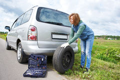 Woman changing a wheel of car on road Royalty Free Stock Image