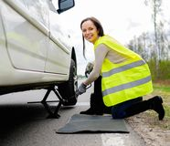Woman changing wheel. On a roadside Stock Image