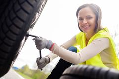 Woman changing wheel. On a roadside Royalty Free Stock Photos