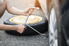 Woman changing wheel on a roadside Royalty Free Stock Photo