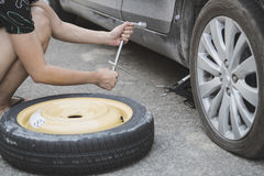 Woman changing wheel on a roadside Royalty Free Stock Image