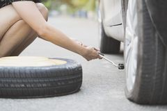 Woman changing wheel on a roadside. Close up Royalty Free Stock Photos