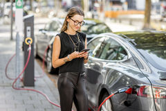Woman charging electric car outdoors. Young woman charging electric car standing with smart phone outdoors on the street in Rotterdam city Royalty Free Stock Photo