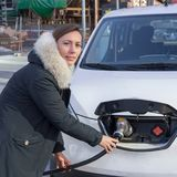 Woman charging an electric car royalty free stock image