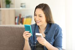 Woman charging phone with a portable charger. Happy woman charging a smart phone with a portable charger sitting on a couch at home stock photography