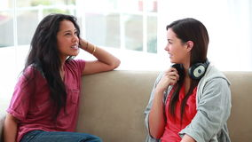 Woman chatting with a friend while holding headphones stock video