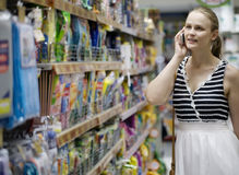 Woman chatting on her mobile while out shopping Royalty Free Stock Image