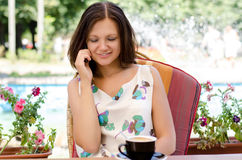 Woman chatting on her mobile phone. Sitting over coffee in a pretty summer garden with flowers Stock Images