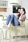 Woman chatting on her mobile phone. Beautiful young woman chatting on her mobile phone in her kitchen stock photos