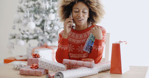 Woman chatting on a mobile as she wraps gifts Royalty Free Stock Images