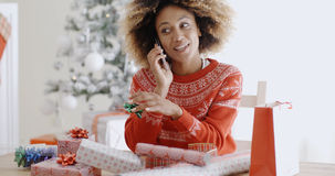Woman chatting on a mobile as she wraps gifts Stock Photos