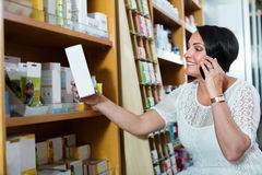 Woman chatting by phone while shopping in drugstore Royalty Free Stock Photography