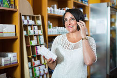 Woman chatting by phone while shopping in drugstore. Happy smiling mature brunette woman chatting by phone while shopping in drugstore royalty free stock image