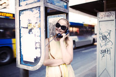 Woman chatting on a public telephone Royalty Free Stock Image
