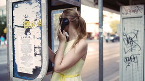 Woman chatting on a public telephone Stock Photo