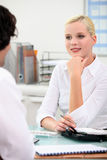 Woman chatting to a colleague Royalty Free Stock Images