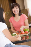 Woman Chatting To Friend While Preparing Meal. In Kitchen royalty free stock photo