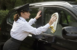 Woman chauffeur polishing car window Royalty Free Stock Photos