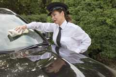 Woman chauffeur polishing car window Royalty Free Stock Photography